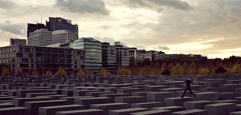 Jumping across the Memorial to the Murdered Jews of Europe in Berlin. Photomontage from Wikipedia.