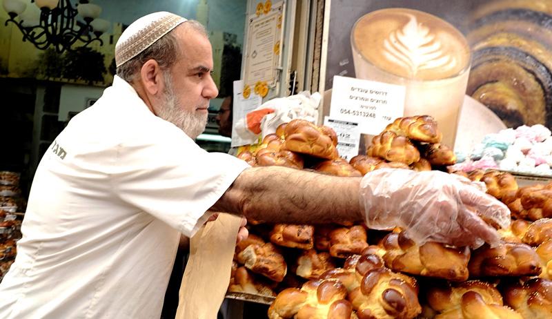 A vendor puts out loaves of hallah in Jerusalem's Mahane Yehuda Market. AP Photo/Robert E. Klein.