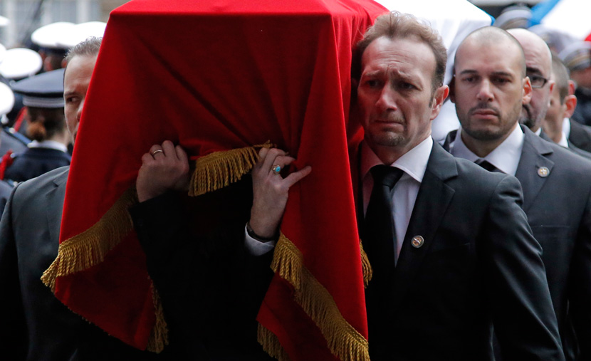 Mourners carry the coffin of Franck Brinsolaro, one of two French police officers killed in the attack on Charlie Hebdo. AP Photo/Francois Mori.
