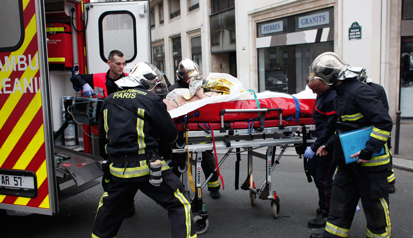 An injured person is transported to an ambulance after the January 7 attack on the satirical newspaper Charlie Hebdo in Paris. AP Photo/Thibault Camus.