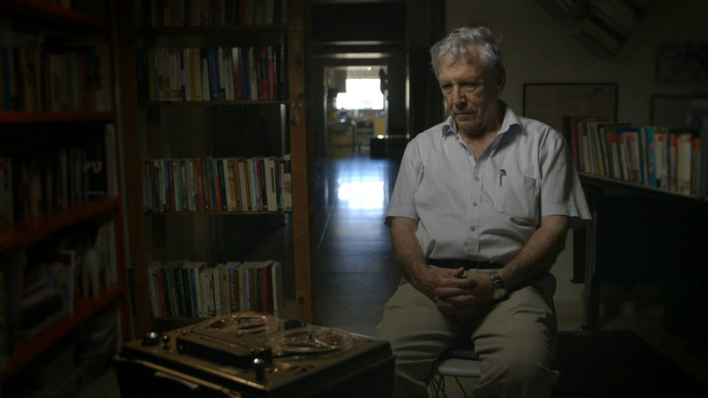 """<span style=""""font-size: smaller;""""><em>Amos Oz listens to testimony he gave after the Six-Day War, in which he fought.</em> Photo by Avner Shahaf.</span>"""