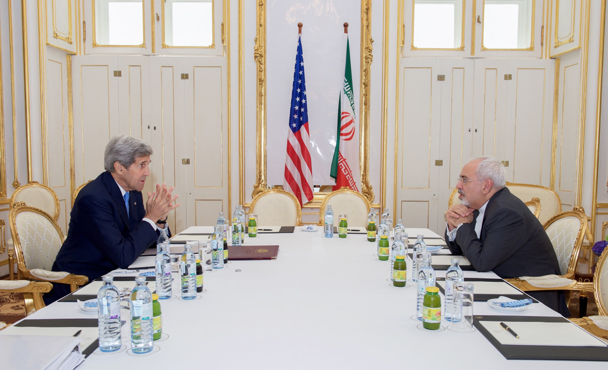 U.S. Secretary of State John Kerry sits across from Iranian Foreign Minister Javad Zarif during a meeting on Iran's nuclear program in Vienna, Austria, on 30 June 2015. Photo by U.S. Department of State /Anadolu Agency/Getty Images.