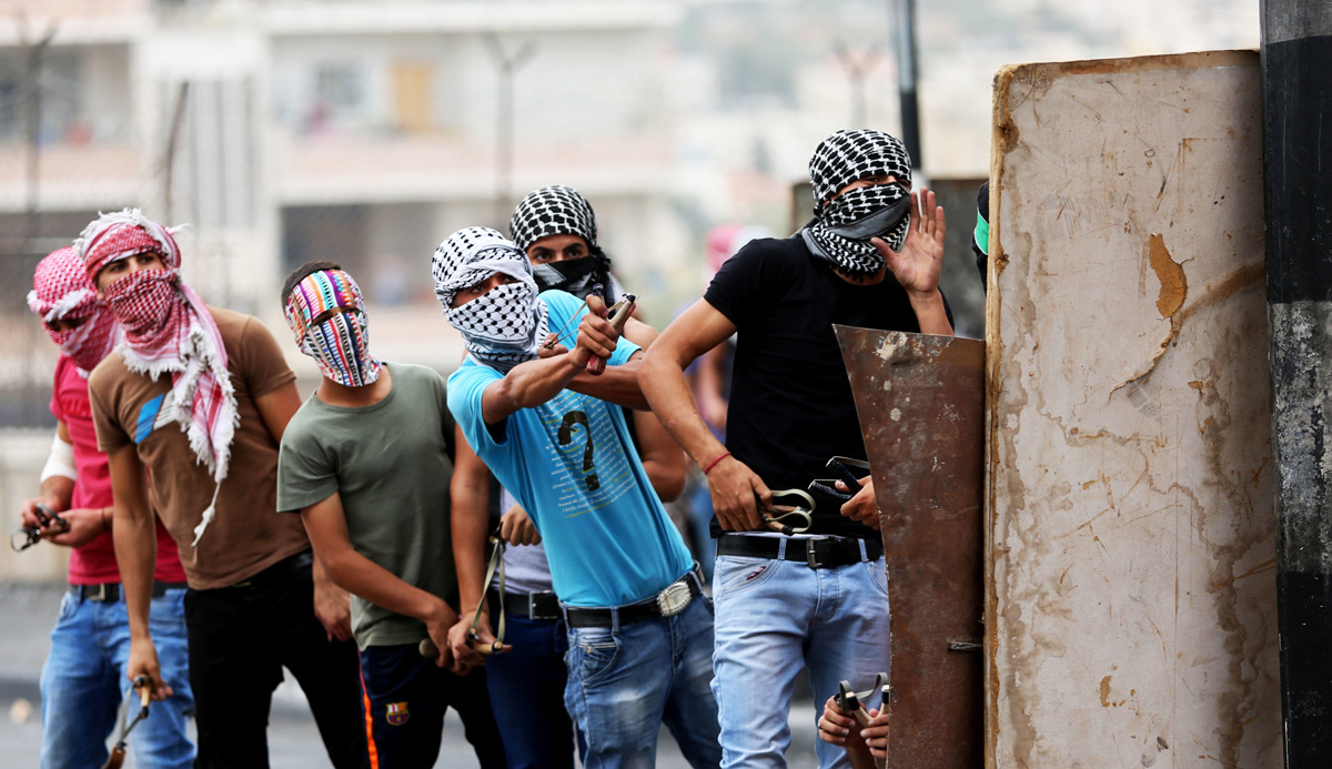 Masked Palestinian youths use slingshots to hurl rocks and marbles at an Israeli military checkpoint in Bethlehem, West Bank on October 23, 2015. Anna Ferensowicz/Pacific Press/LightRocket via Getty Images.