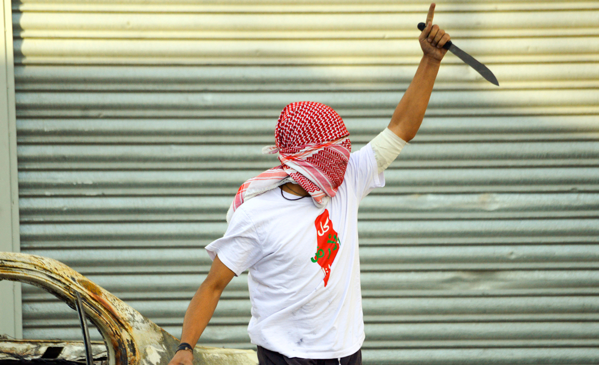 A Palestinian demonstrator raises a knife during clashes with Israeli police in the Shuafat refugee camp in Jerusalem, Friday, Oct. 9, 2015. AP Photo/Mahmoud Illean.