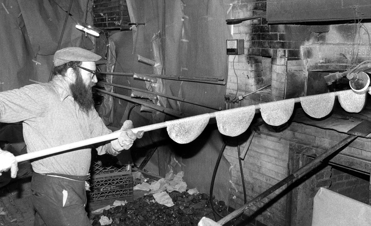 A man baking round handmade shmurah matzah. Anthony Pescatore/NY Daily News Archive via Getty Images.