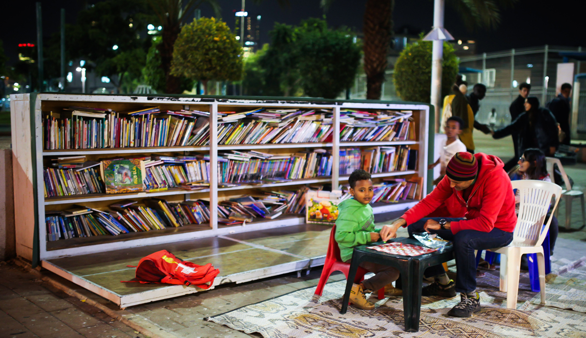 A child and a man sit together at an outdoor book garden in Tel Aviv, December 9, 2015. Esther Rubyan/Flash90.