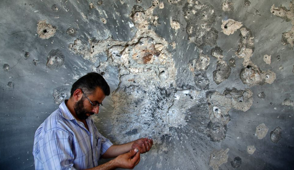 A Syrian man holds bullets he picked from the wall of a damaged house in the town of Atareb, on the outskirts of Aleppo. AP Photo/Khalil Hamra.