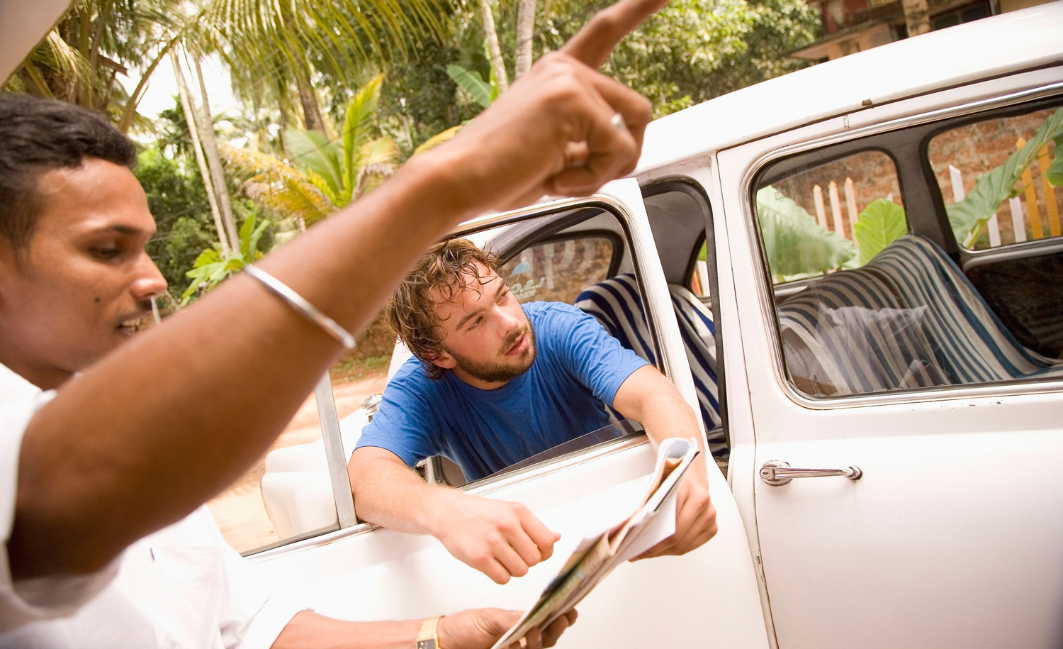 A taxi driver pointing out directions to a backpacker. Design Pics Inc/Alamy Stock Photo.