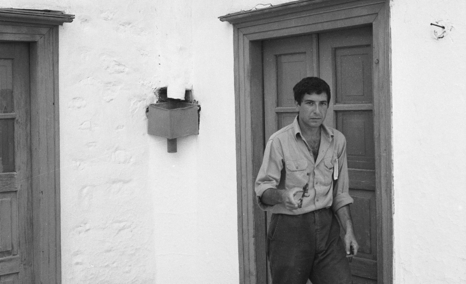 Leonard Cohen walking on a street near his vacation home in Hydra, Greece, October 1960. James Burke/The LIFE Picture Collection/Getty Images.