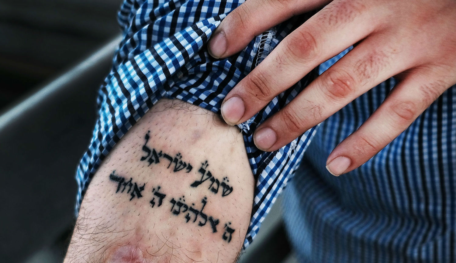 A patient at a Brooklyn methadone clinic looks to a tattoo of the Sh'ma prayer in his fight with addiction. Spencer Platt/Getty Images.