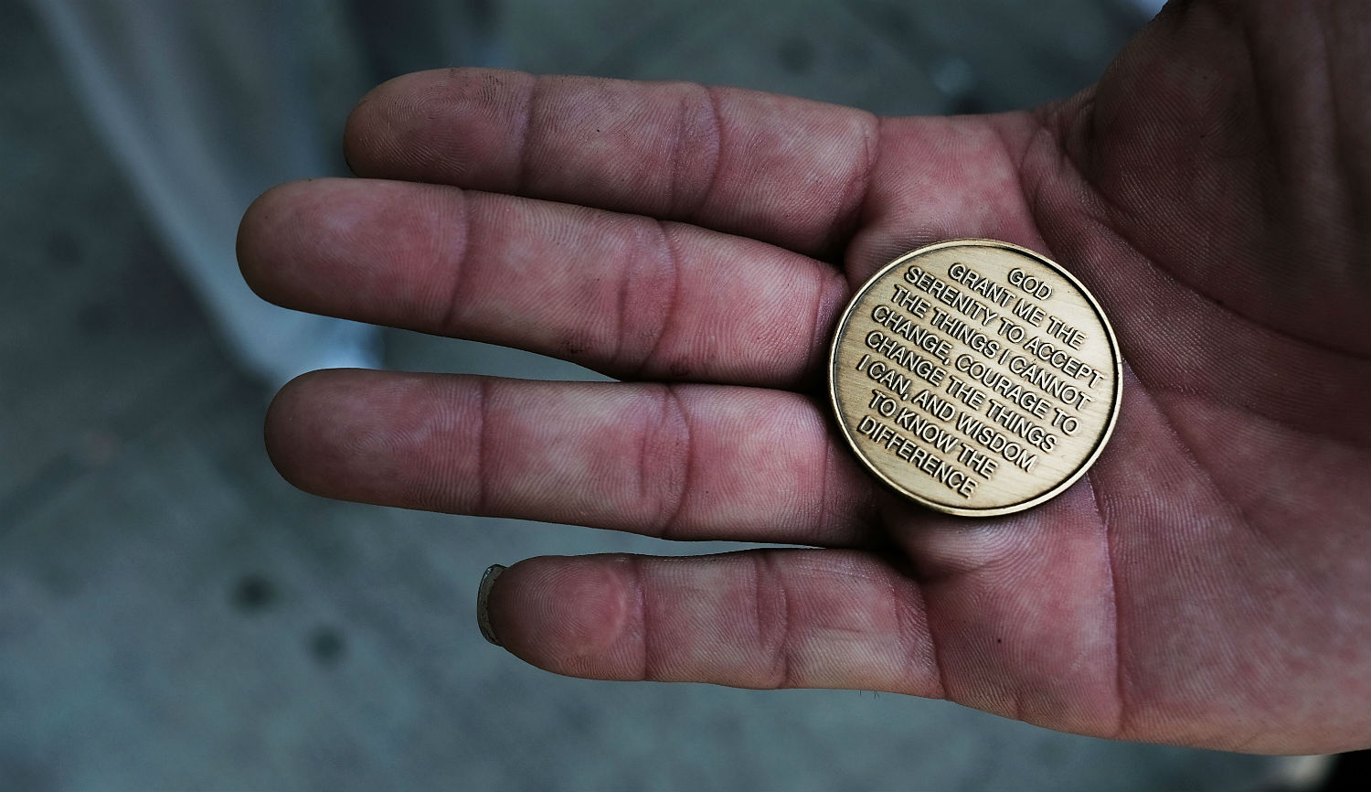 A patient at a Brooklyn methadone clinic holds a coin with the Serenity Prayer on it. Spencer Platt/Getty Images.