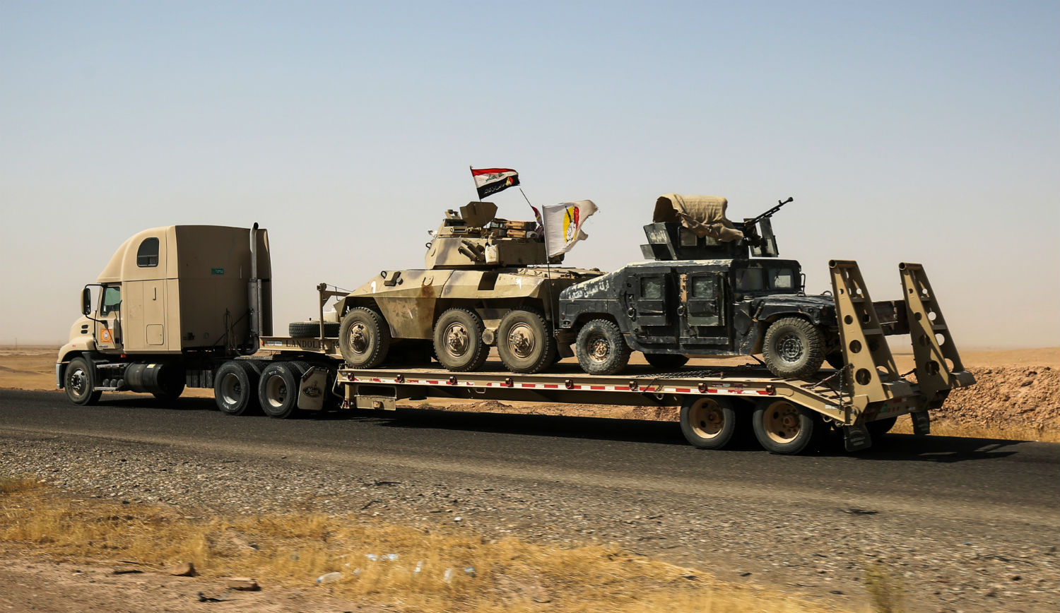 A truck tows armored combat vehicles belonging to an Iraqi anti-Islamic State paramilitary group on August 31, 2017. AHMAD AL-RUBAYE/AFP/Getty Images.