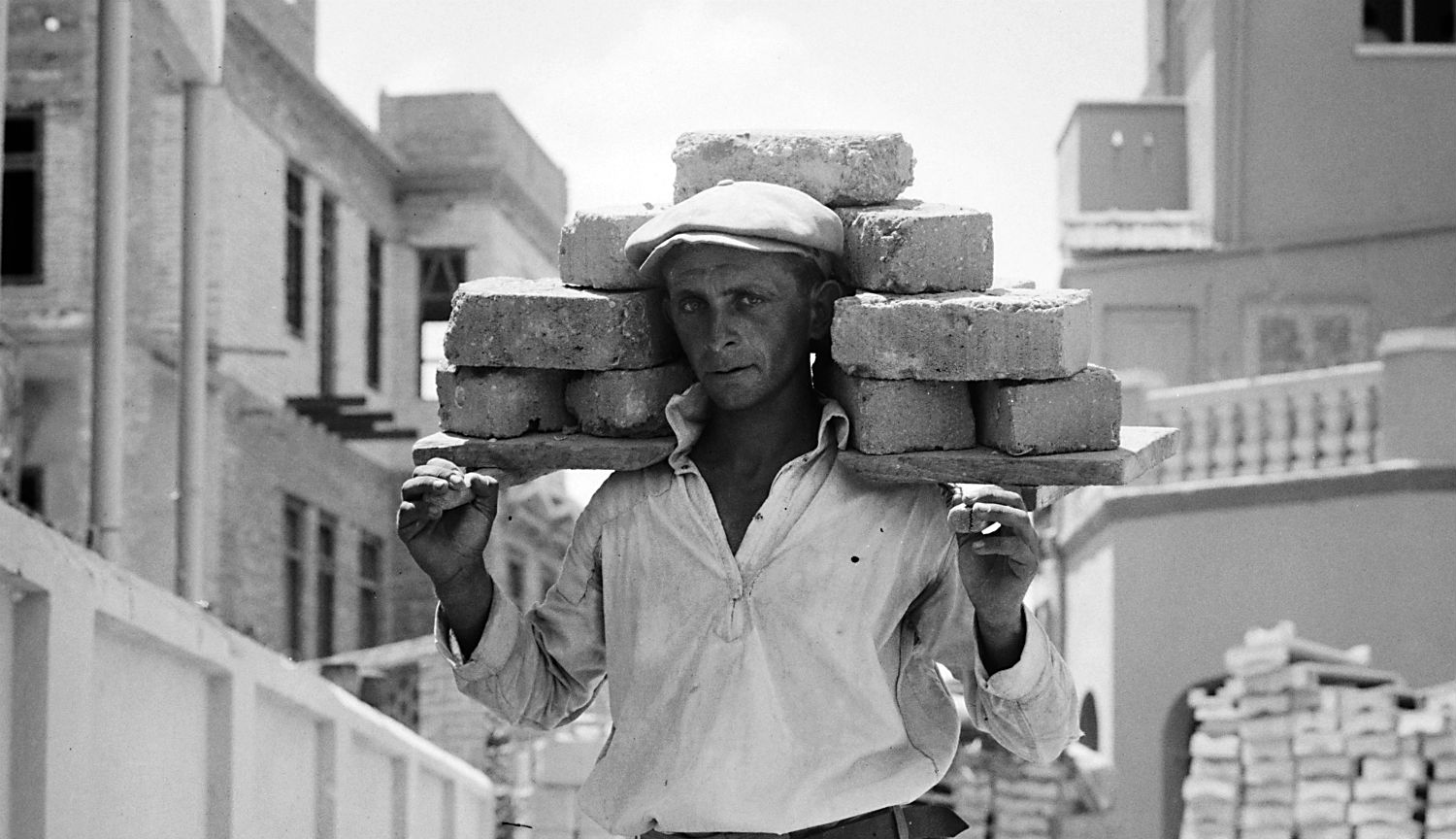 A man carrying bricks in 1920s Tel Aviv. Library of Congress.