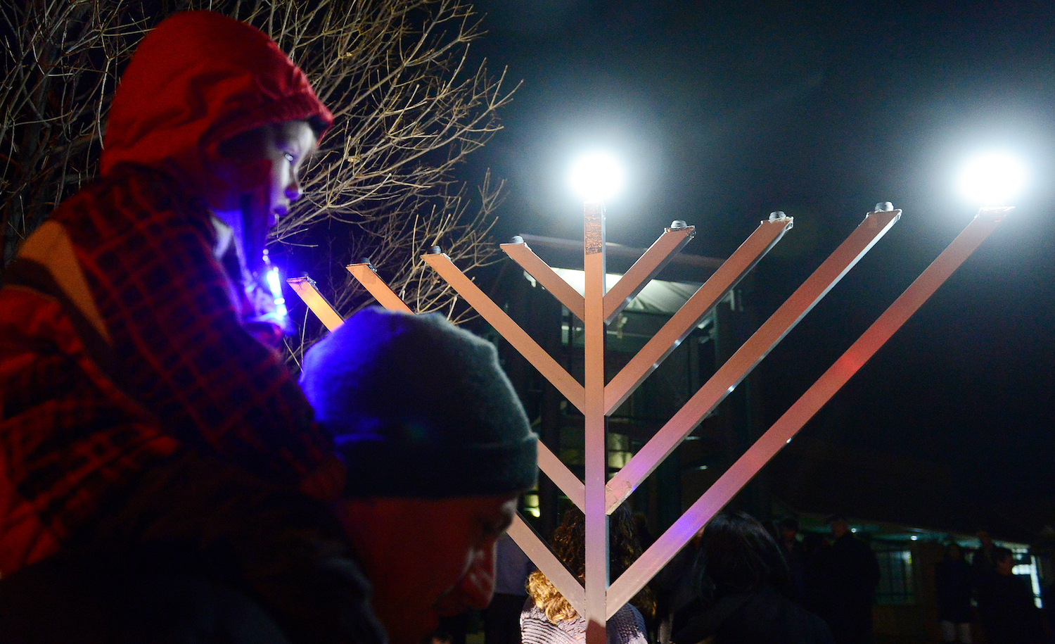 A child on his father's shoulders on the first night of Hanukkah. Brent Lewis/The Denver Post via Getty Images.