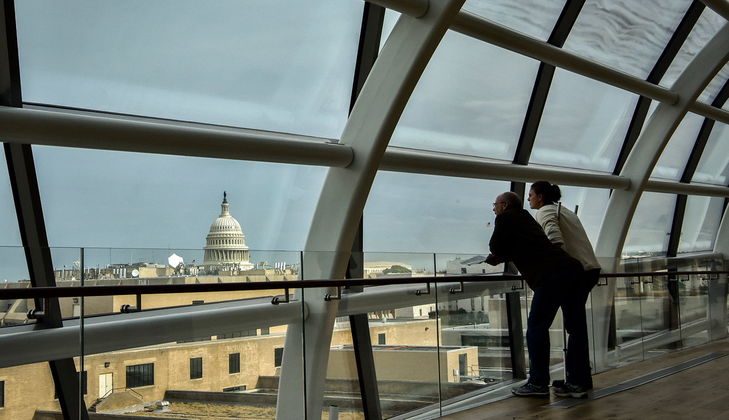 A pair of visitors takes in the view from an atrium at the Museum of the Bible in Washington, D.C. Bill O'Leary/The Washington Post via Getty Images.