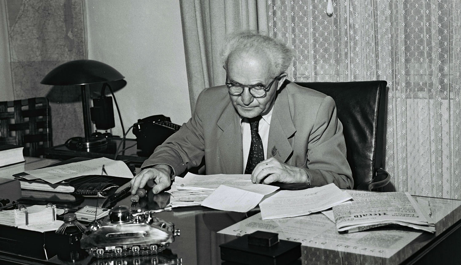 David Ben-Gurion in his Tel Aviv office on September 1, 1949 in Tel Aviv. The model of a tank on his desk is a cigarette box and lighter given to him by an Israeli soldier. GPO via Getty Images.
