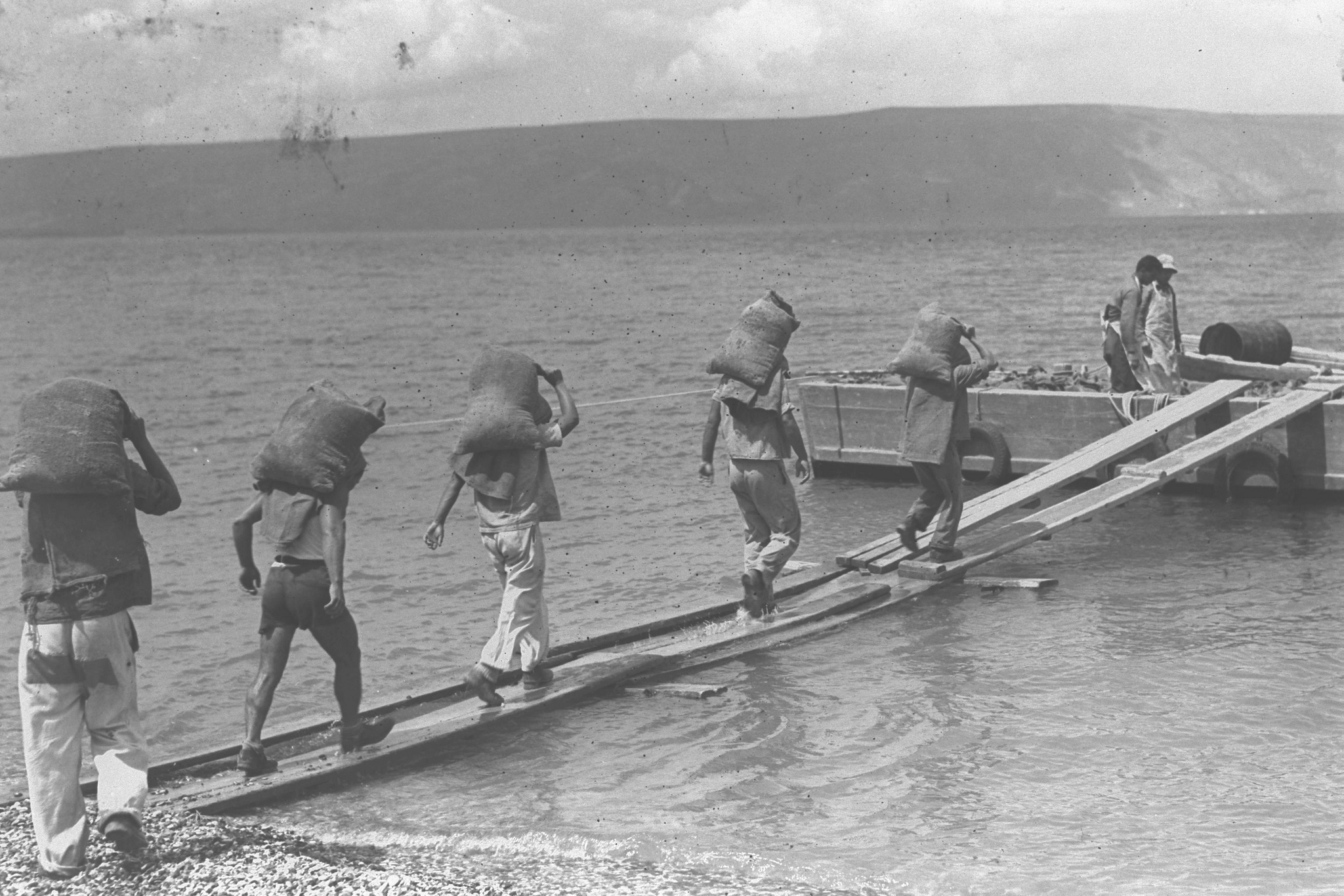 Men build the breakwater of a fishing port on the eastern shore of the Sea of Galilee in the early 20th century. Zoltan Kluger/Government Press Office.