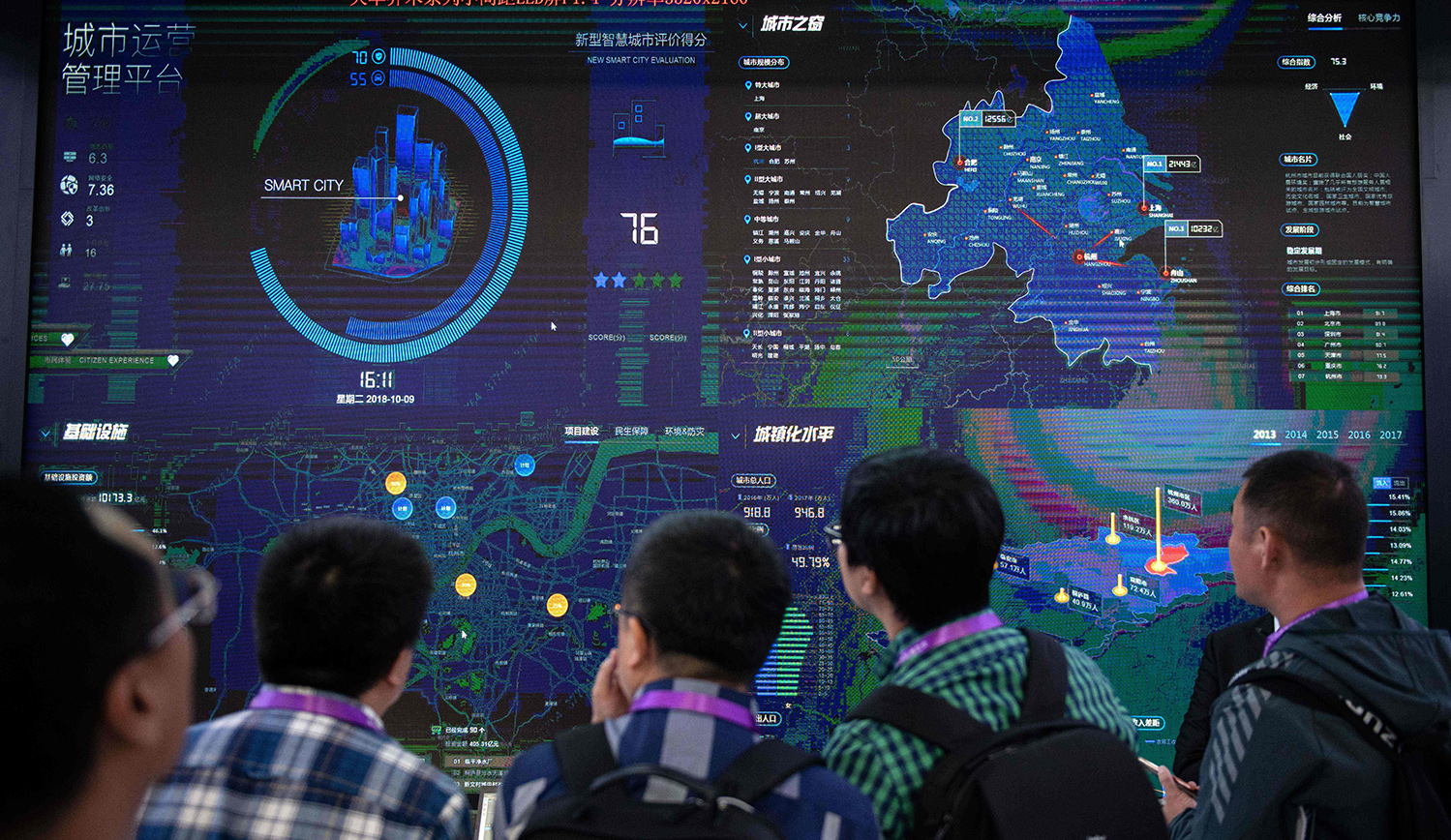 Visitors look at an AI security software program on a screen at the 14th China International Exhibition on Public Safety and Security in Beijing on October 24, 2018. NICOLAS ASFOURI / AFP.