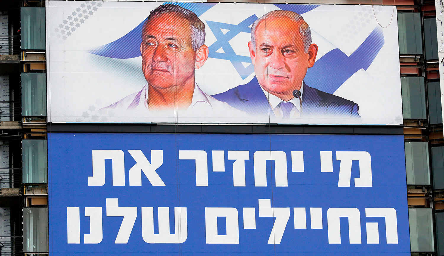 "Benny Gantz and Benjamin Netanyahu on an election billboard in Tel Aviv in March 2019. The Hebrew reads ""Who will bring back our soldiers?"" JACK GUEZ/AFP/Getty Images."