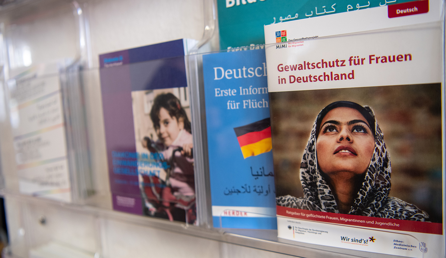 Information brochures shelf in a shelter for refugee women in Germany. Monika Skolimowska/picture alliance via Getty Images.