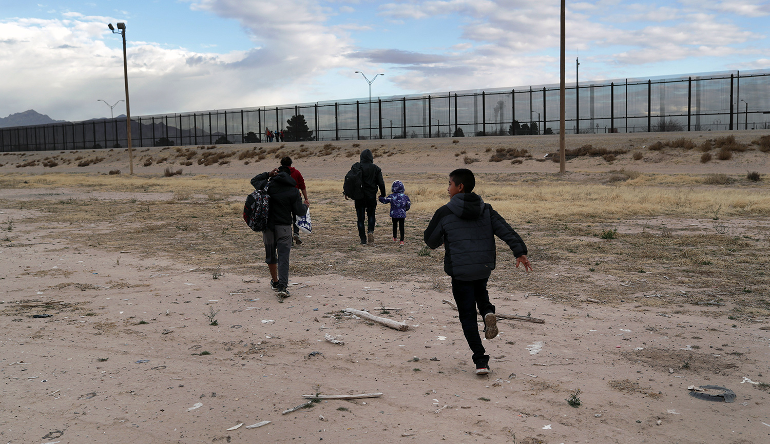Central American immigrants walk toward the border fence after crossing the Rio Grande from Mexico on February 1, 2019 in El Paso, Texas. John Moore/Getty Images.
