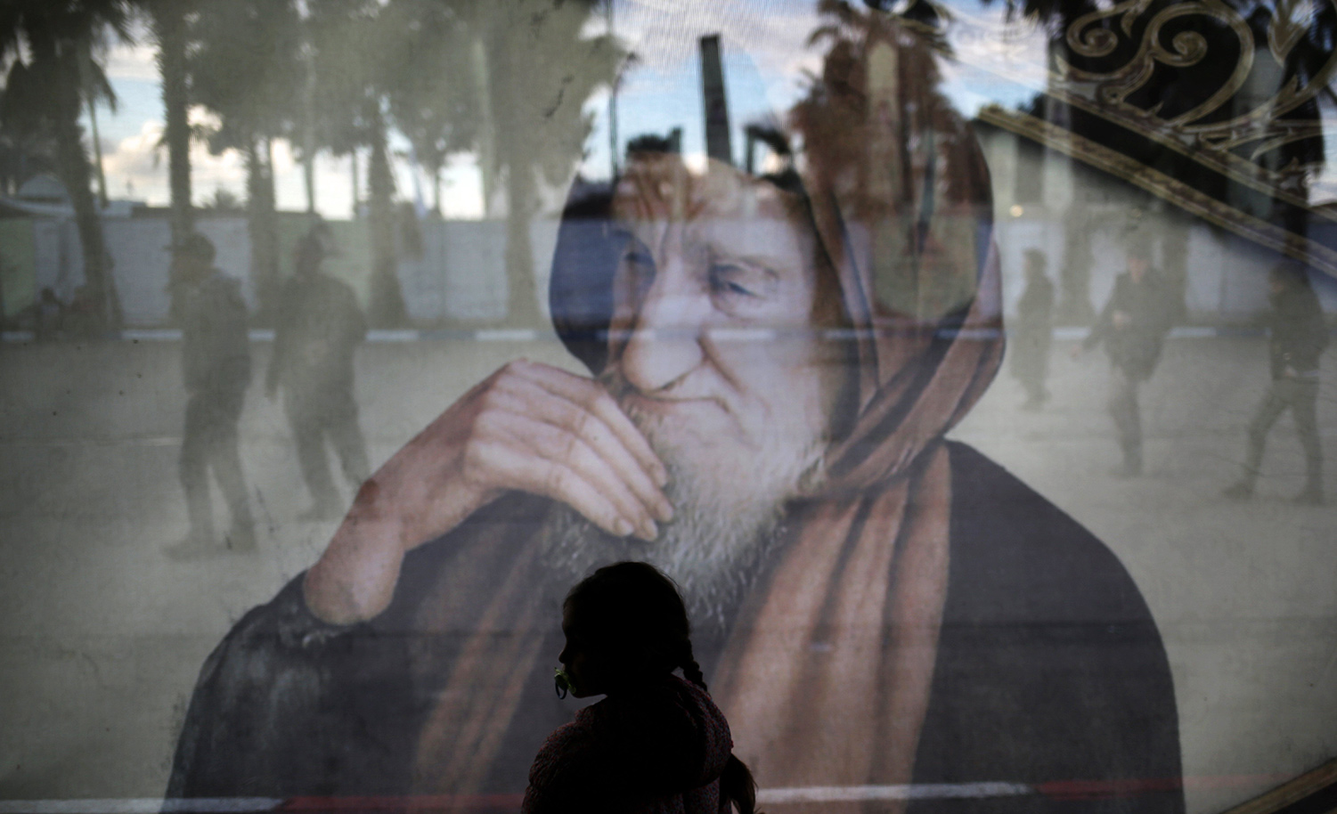 Israeli Jews walk past an image of Rabbi Israel Abuhatseira, known as the Baba Sali, during the annual pilgrimage to his grave in the southern Israeli town of Netivot, on January 31, 2017. MENAHEM KAHANA/AFP/Getty Images.