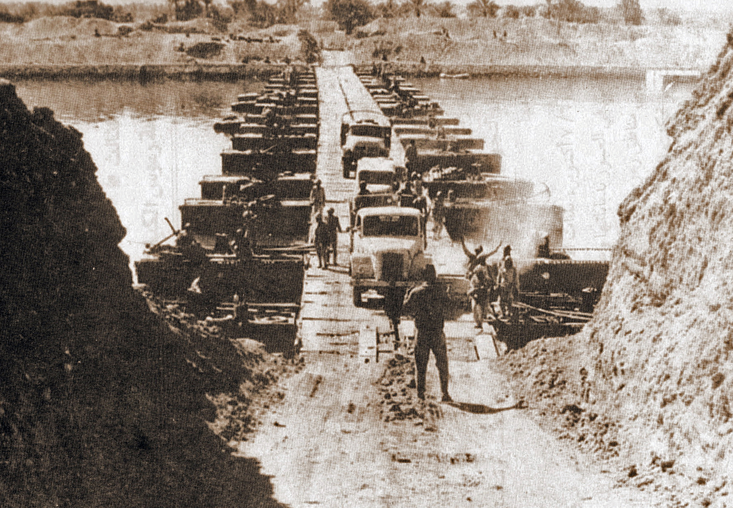 Egyptian military trucks cross a bridge laid over the Suez Canal on October 7, 1973 during the Yom Kippur War. CIA via Wikipedia.