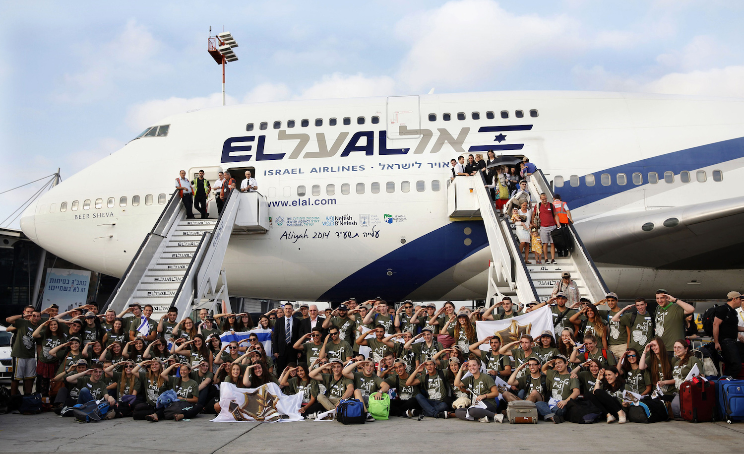 Israeli President Reuven Rivlin and Interior Minister Gideon Saar (C-L) pose at Ben Gurion Airport with new immigrants to Israel on August 12, 2014. GALI TIBBON/AFP via Getty Images.