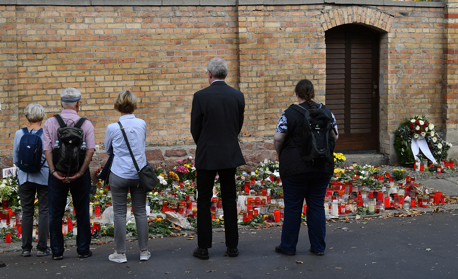 People standing in front of candles and flowers at the synagogue in Halle, Germany after a right-wing extremist attack on October 9, 2019. Photo by Hendrik Schmidt via Getty Images.