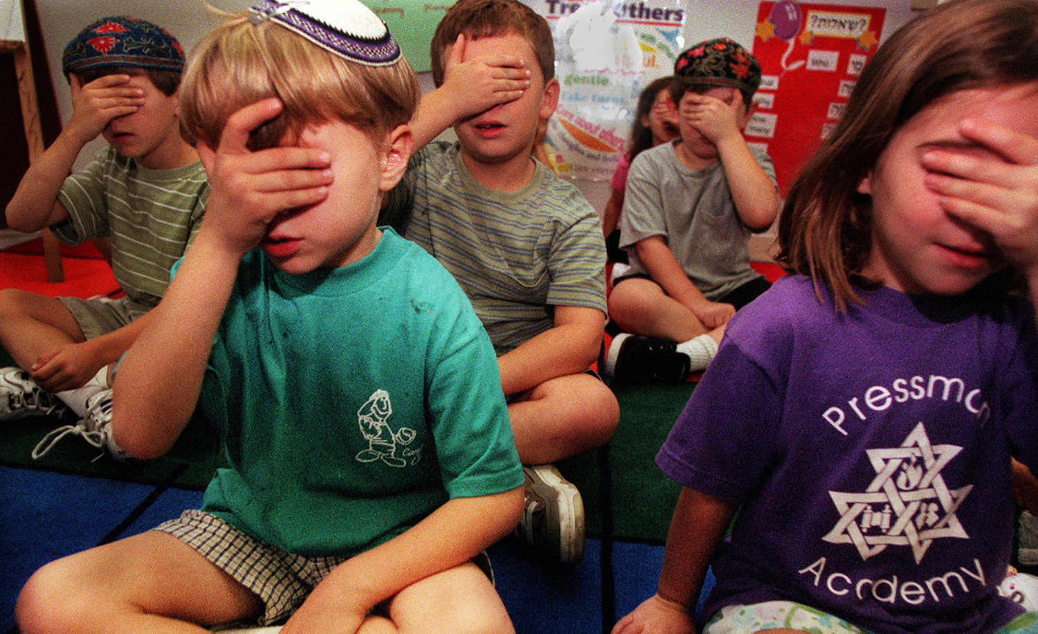 Children covering their eyes during the Sh'ma on September 28, 2000 at Pressman Academy in Los Angeles. Bob Chamberlin/Los Angeles Times via Getty Images.