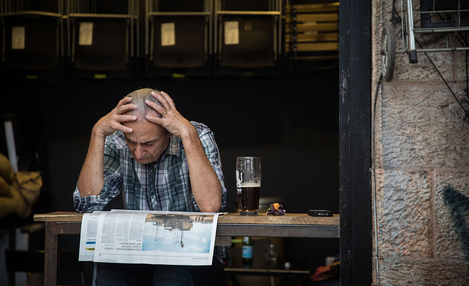 A man reads the newspaper at a cafe at the Mahane Yehuda Market in Jerusalem on September 5, 2017. Hadas Parush/Flash90.
