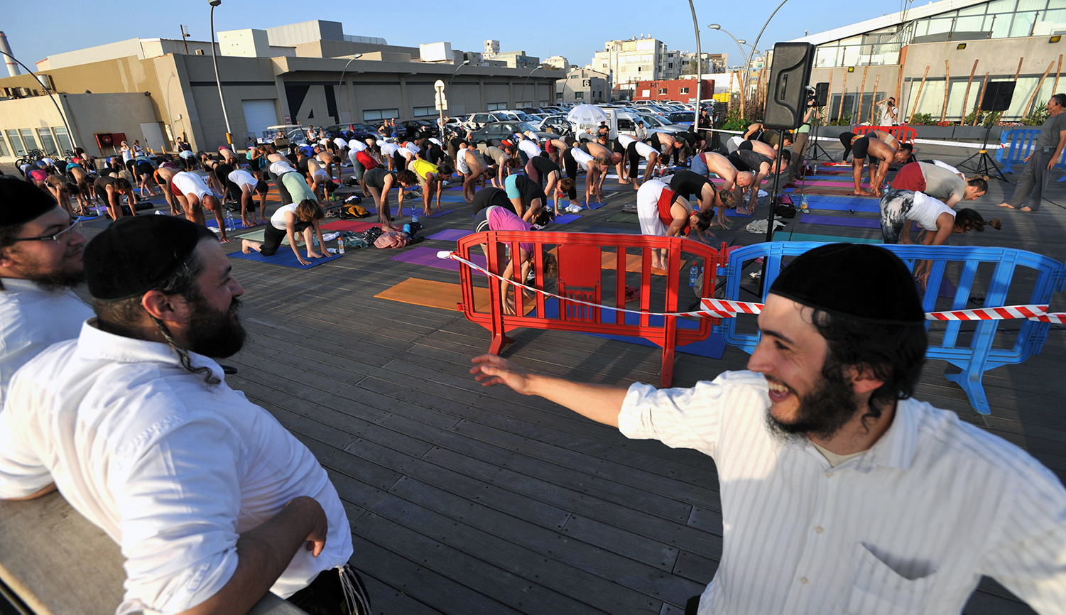 Orthodox Israeli Jewish men watch as other Israelis gather in Tel Aviv for a mass outdoor yoga session to mark the longest day of the year on June 21, 2010. YEHUDA RAIZNER/AFP via Getty Images.
