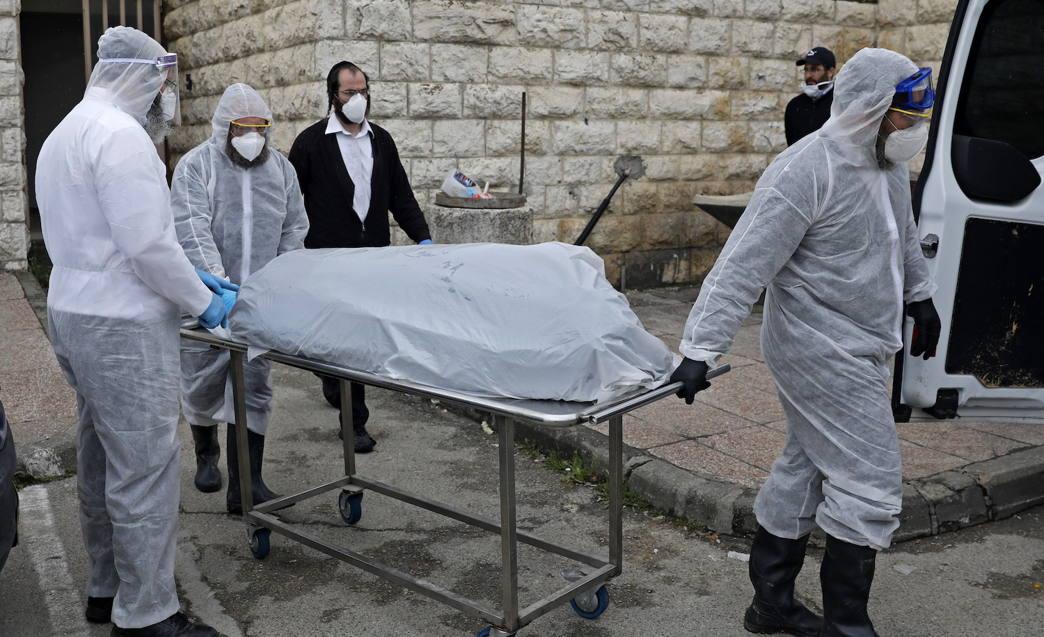 Israeli workers transporting the body of a patient who died from complications of coronavirus in Jerusalem on April 1, 2020. AHMAD GHARABLI/AFP via Getty Images.