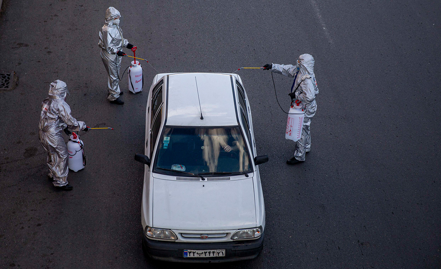 Volunteers spraying disinfectant on a car during the coronavirus pandemic on March 31, 2020 in Tehran. Majid Saeedi/Getty Images.
