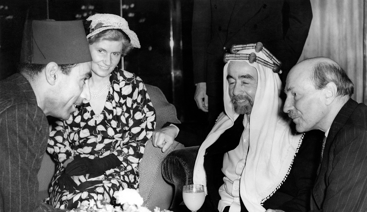 King Abdullah I of Jordan talking to a member of the Transjordanian Legation at the Dorchester Hotel, London, on September 1, 1949. With him are British Prime Minister Clement Attlee and Attlee's wife Violet. Edward Miller/Keystone/Hulton Archive/Getty Images.