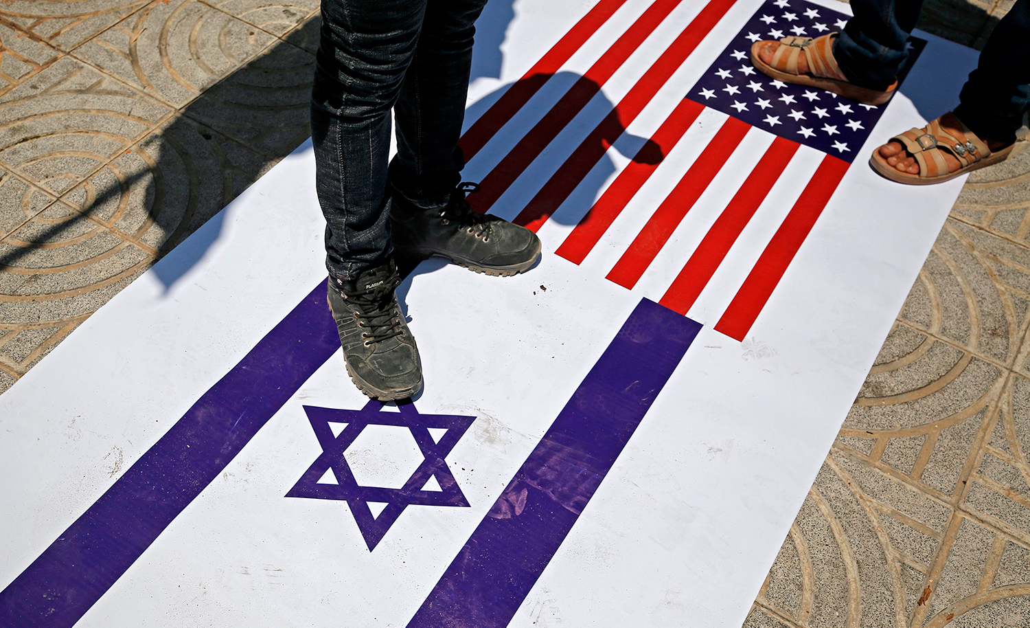 Palestinians trample a poster on the ground depicting the flags of Israel and the US on July 7, 2020. MOHAMMED ABED/AFP via Getty Images.
