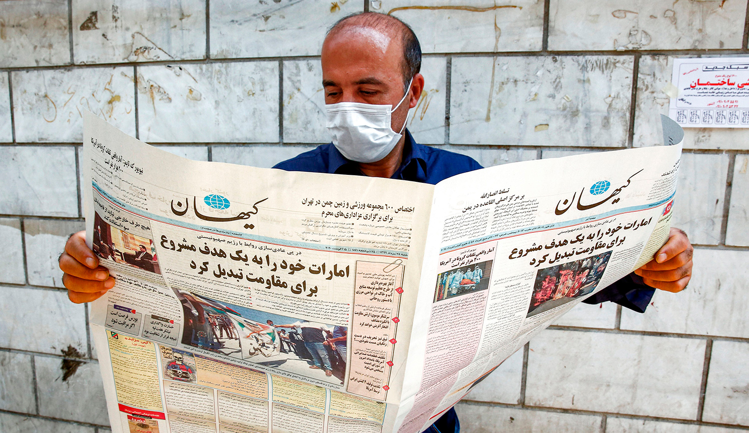 """A man in Tehran looking at a Farsi newspaper with a headline declaring """"The UAE has become a legitimate and easy target."""" AFP via Getty Images."""