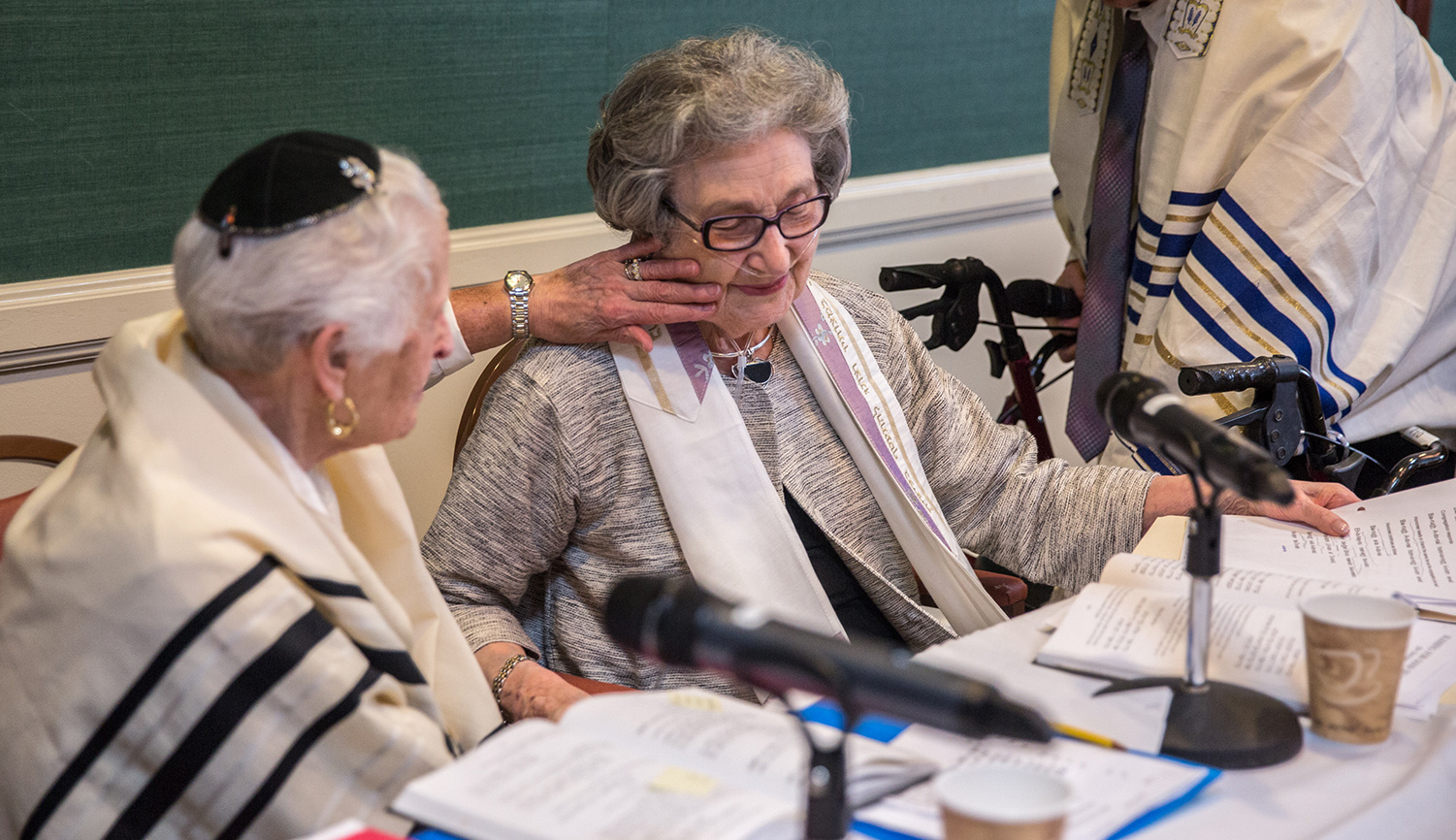 Charlotte Markowitz, 85, congratulates Sy Laufe, 90, after Sy read from the Torah at their bat mitzvah ceremony, at the Five Star Residences in Chevy Chase, Maryland, May 14, 2016. Evelyn Hockstein/For The Washington Post via Getty Images.