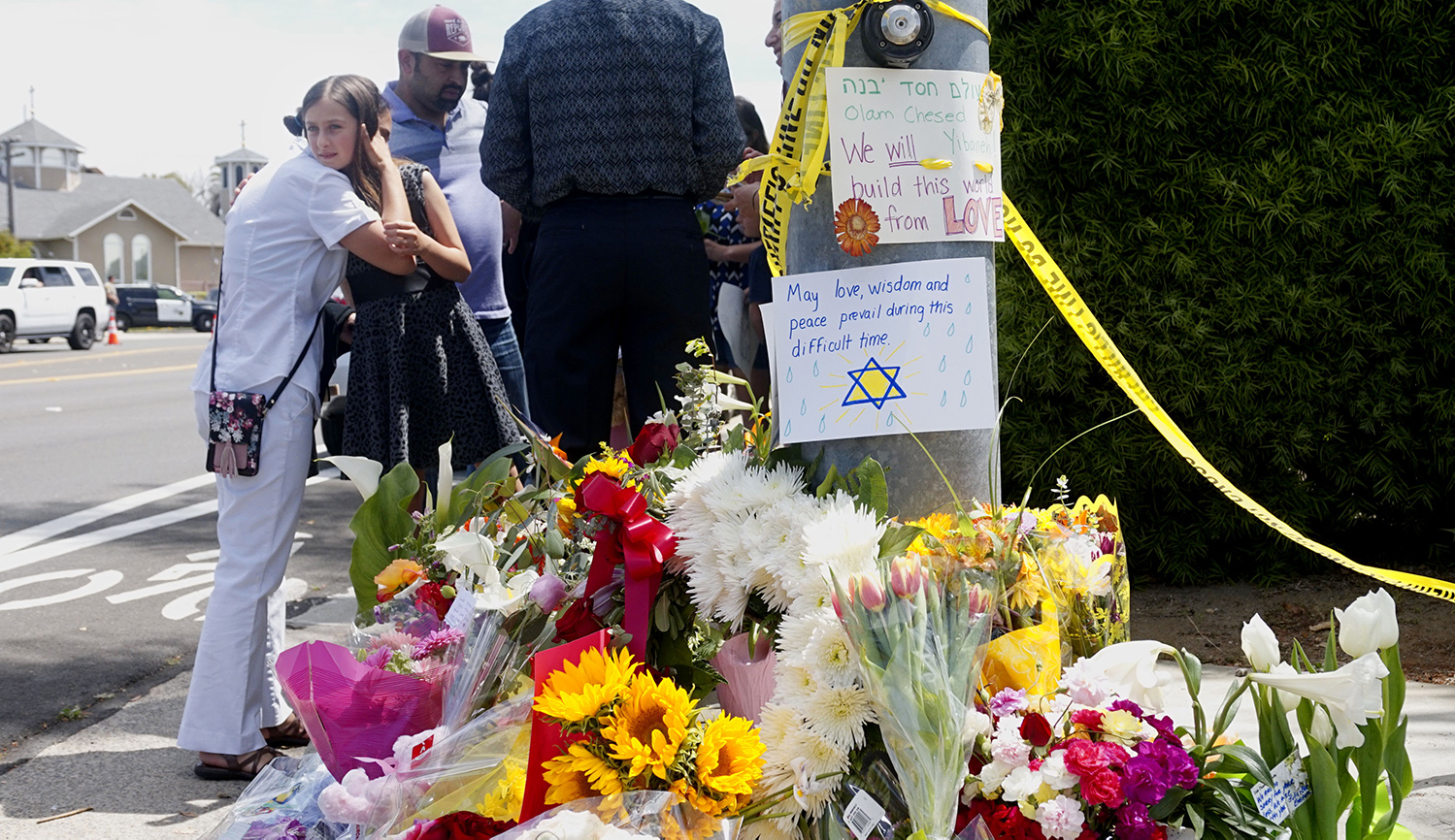 Mourners and well wishers leave flowers and signs at a memorial across the street from the Chabad of Poway Synagogue on Sunday, April 28, 2019 in Poway, California, one day after a teenage gunman opened fire, killing one person and injuring three others. SANDY HUFFAKER/AFP via Getty Images.