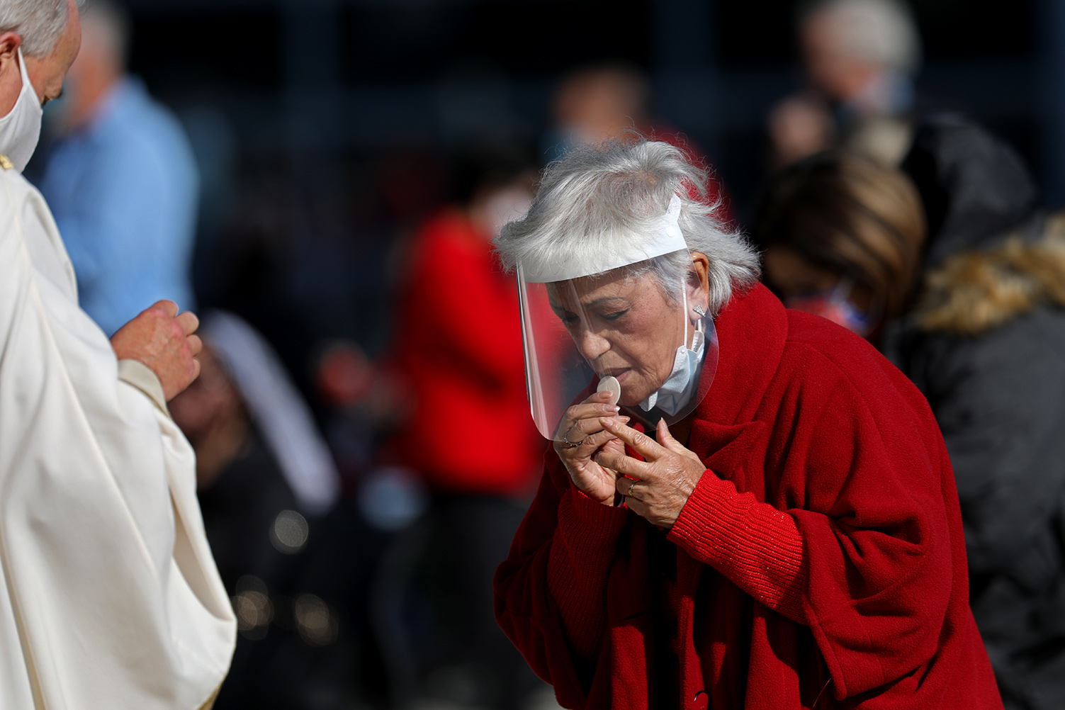 A parishioner takes communion while attending a Christmas Day mass given outdoors on Friday, Dec. 25, 2020 in Garden Grove, CA. Gary Coronado/Los Angeles Times via Getty Images.