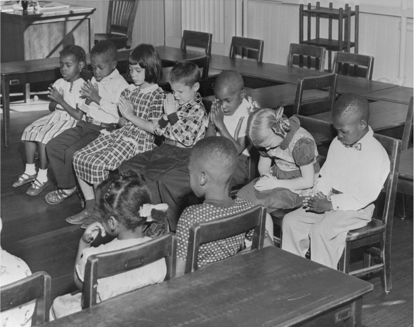 White and black pupils at Seaton Elementary School in Washington, DC join in a prayer as their school opens on a non-segregated basis for the first time on September 13, 1954. Bettmann via Getty Images.