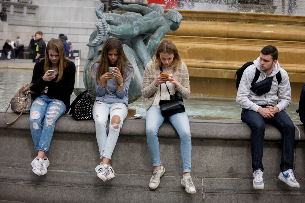 In London, three teenage girls are intently focused on their smartphones while a young man looks on. Photo by In Pictures Ltd./Corbis via Getty Images.