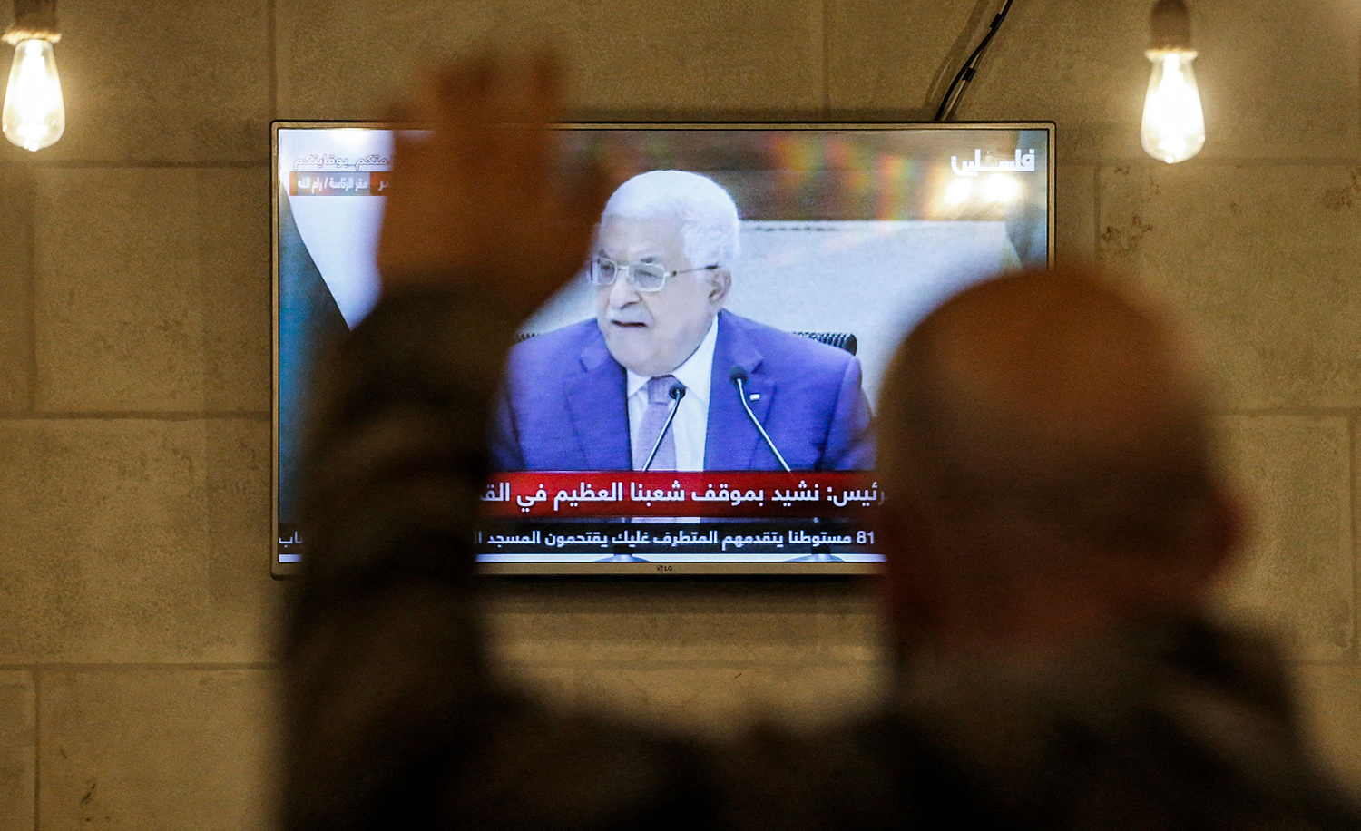 A Palestinian in a coffee shop in Hebron on April 29, 2021 watches a speech by president Mahmoud Abbas. HAZEM BADER/AFP via Getty Images.