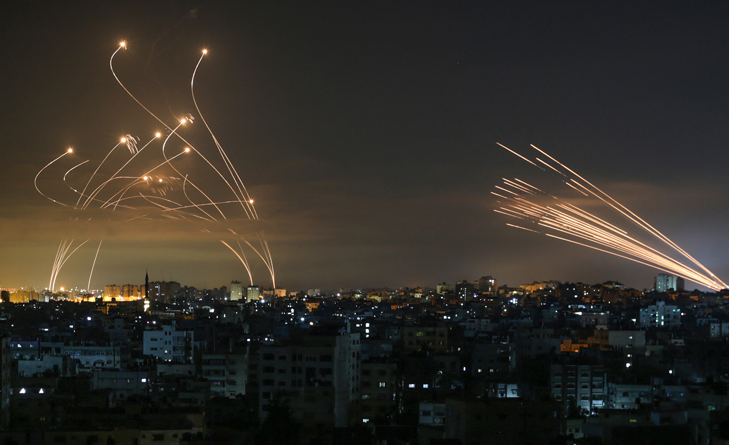 Streaks of light appear as Israel's Iron Dome anti-missile system intercepts rockets launched from the Gaza Strip on May 16, 2021. ANAS BABA/AFP via Getty Images.