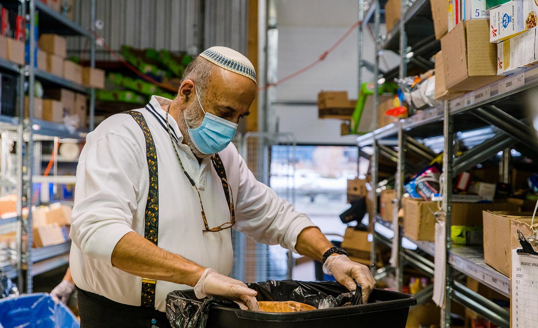 A volunteer prepares meals at Chasdei Kaduri Jewish Food Bank in Toronto in November 2020. Shawn Goldberg/SOPA Images/LightRocket via Getty Images.