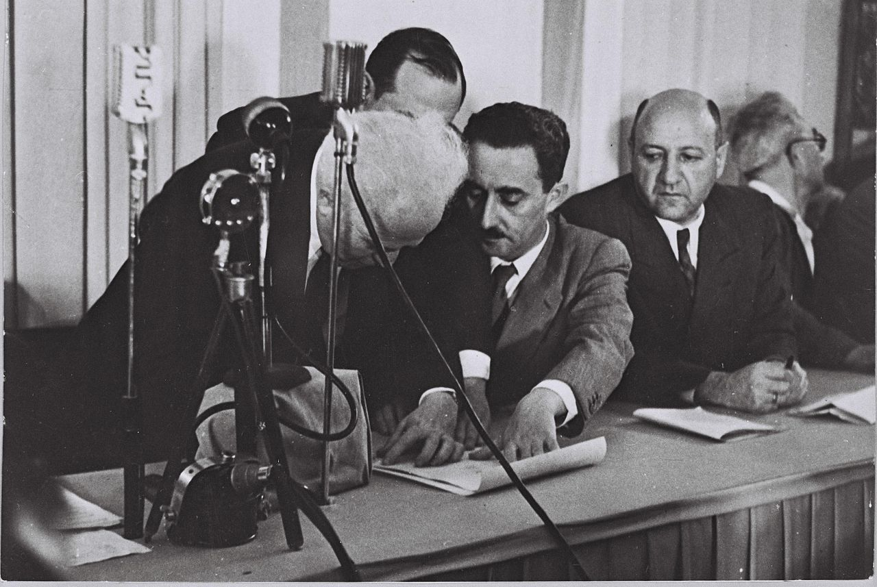 David Ben-Gurion signing the Israeli Declaration of Independence held by Moshe Sharett with Eliezer Kaplan looking on on May 14, 1948. National Photo Collection of Israel.