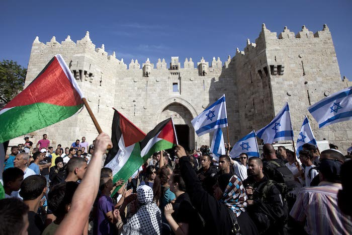 <em>Israelis and Palestinians wave flags as Israelis march celebrating Jerusalem Day outside Damascus Gate in Jerusalem's old city on Wednesday, May 8, 2013.</em> Credit: Associated Press/Sebastian Scheiner.