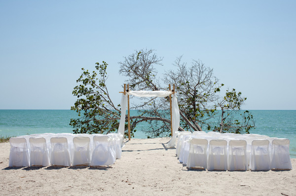 Wedding on the beach, chairs and huppah. © Matthew Valentine | Dreamstime.com.