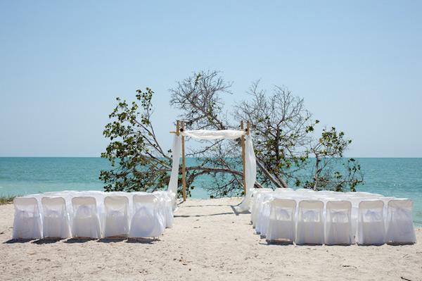 Wedding on the beach, chairs and huppah. © Matthew Valentine | Dreamstime.com.
