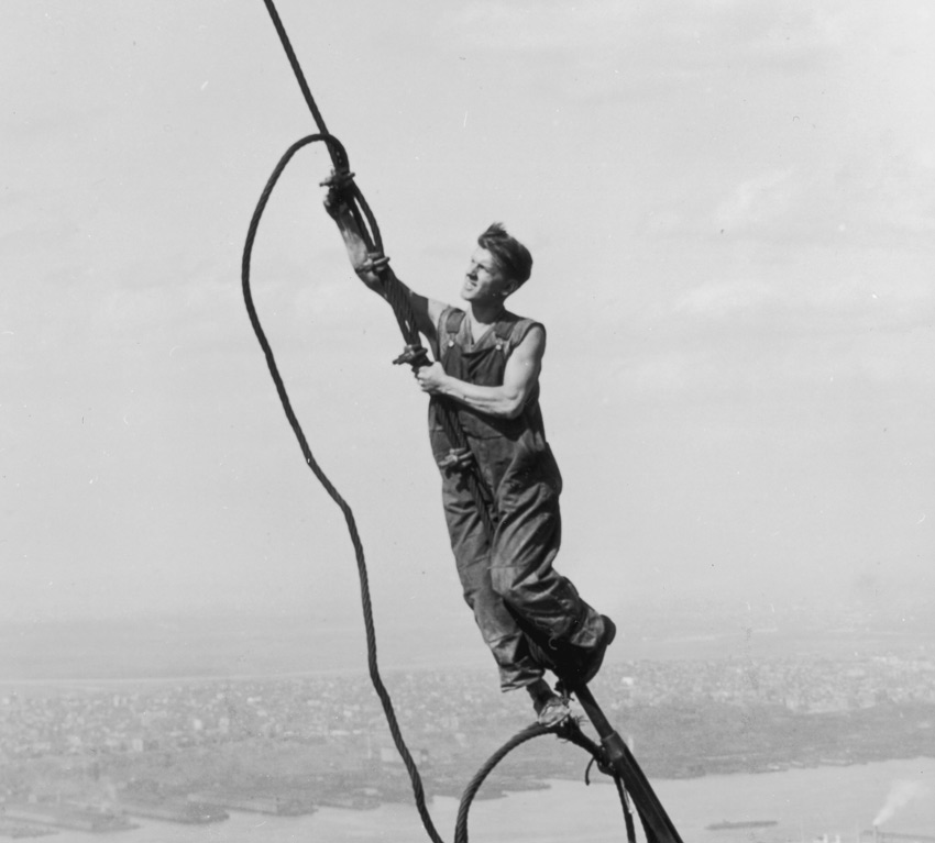 <em>A construction worker connects two cables suspended high above the New York during the construction of the Empire State Building, 1931.</em> Photo credit: Lewis W. Hine/George Eastman House/Getty Images.